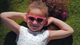 St?ende av ett gulligt barn, en underbar liten h?rlig flicka i en vit kl?nning och rosa exponeringsglas som ligger p? gr?set arkivfilmer