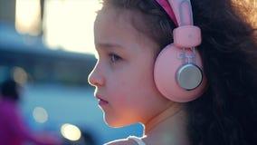 St?ende av ett gulligt barn med lockigt h?r, Caucasian liten flicka i en rosa kl?nning med en rosa blomma p? hennes huvud i henne arkivfilmer