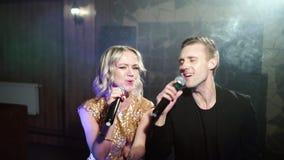 St?ende av ett ungt par som sjunger med en mikrofon i en karaokest?ng lager videofilmer