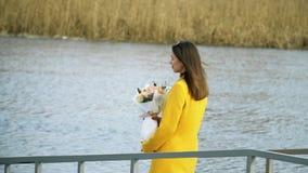 St?ende av flickan som utomhus g?r p? flodstranden med blommor, h?rt begrepp f?r f?rh?llande stock video