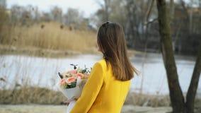 St?ende av flickan som utomhus g?r p? flodstranden med blommor, h?rt begrepp f?r f?rh?llande arkivfilmer