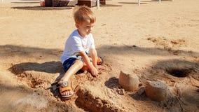 St?ende av gulliga 3 ?r gammal litet barnpojke som sitter p? den sandiga stranden och spelar med leksaker och den byggande sandsl royaltyfri bild
