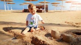 St?ende av gulliga 3 ?r gammal litet barnpojke som sitter p? den sandiga stranden och spelar med leksaker och den byggande sandsl arkivbilder