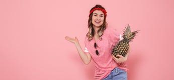 St?ende av hipsterflickan i exponeringsglas och ananas p? rosa bakgrund royaltyfri bild