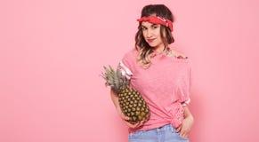 St?ende av hipsterflickan och ananas som isoleras p? rosa bakgrund royaltyfri fotografi