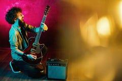 St?ende av hipstermannen med lockigt h?r med den r?da gitarren i neonljus leka rock skjuten studio f?r elektrisk gitarrmusiker royaltyfria bilder