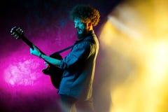 St?ende av hipstermannen med lockigt h?r med den r?da gitarren i neonljus leka rock skjuten studio f?r elektrisk gitarrmusiker royaltyfria foton