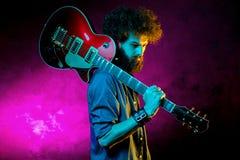 St?ende av hipstermannen med lockigt h?r med den r?da gitarren i neonljus leka rock skjuten studio f?r elektrisk gitarrmusiker royaltyfri foto
