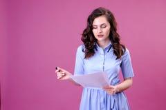St?ende av kvinnan med ett papper och en penna som g?r listan och t?nker ?ver rosa bakgrund royaltyfria foton