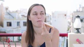 St?ende av kvinnan som har en frukost i kaf? p? terrass lager videofilmer