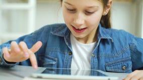 St?ende av lilla flickan som spelar online spel p? minnestavlan arkivfilmer