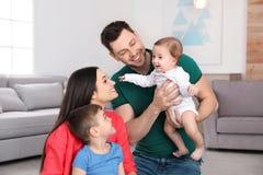 St?ende av lyckliga f?r?ldrar och deras gulliga barn Familj Tid arkivbilder
