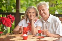 St?ende av lyckliga h?ga par som dricker kaffe royaltyfria foton