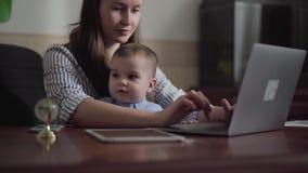 St?ende av modern och den lilla sonen som inomhus placeras med en b?rbar dator p? tabellen Upptagen ung moder som hemma arbetar _ stock video