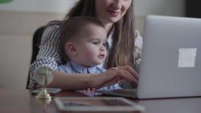 St?ende av modern och den lilla sonen som inomhus placeras med en b?rbar dator p? tabellen Upptagen ung moder som hemma arbetar _ lager videofilmer