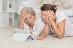 St?ende av modern och hennes vuxna dotter som ligger p? golv och ser minnestavlan fotografering för bildbyråer