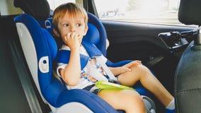 St?ende av 3 ?r gammal litet barnpojke som sitter i barns?kerhetsplats i bil och ?ter kakor Ungar som in reser fotografering för bildbyråer