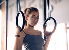 St?ende av sportkvinnautbildning med gymnastiska cirklar i idrottshallen Kondition och sunt livsstilbegrepp arkivfoto