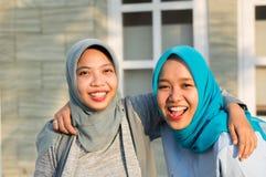 St?ende av tv? lyckliga hijabkvinnor som ler p? kameran, medan omfamna framme av deras hus royaltyfri fotografi