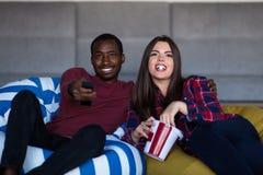St?ende av unga par som sitter p? soffan som h?ller ?gonen p? en film med uttryck p? deras framsidor arkivfoto
