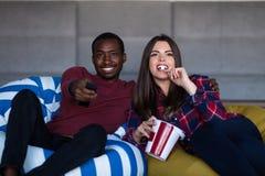 St?ende av unga par som sitter p? soffan som h?ller ?gonen p? en film med uttryck p? deras framsidor fotografering för bildbyråer