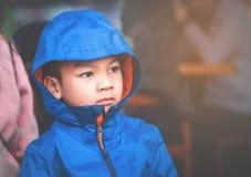 St?ende av ungepojken i bl?a vinterkl?der royaltyfri fotografi