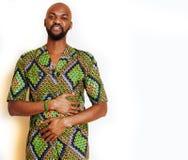 St?ende av ungt stiligt afrikanskt b?ra f?r man som ?r ljust - gr?n nationell dr?kt som ler att g?ra en gest, underh?llningmateri fotografering för bildbyråer