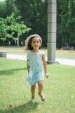 St?enden av att le afrikansk amerikanliten flickaspring parkerar in fotografering för bildbyråer