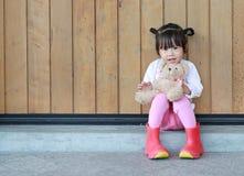 St?enden av den gulliga lilla flickan sitter och krama Teddy Bear mot den wood plankav?ggen royaltyfri foto