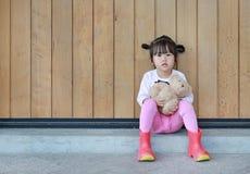 St?enden av den gulliga lilla flickan sitter och krama Teddy Bear mot den wood plankav?ggen royaltyfri fotografi