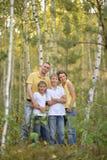 St?enden av den lyckliga familjen av fyra i h?st parkerar arkivbilder