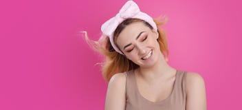 St?enden av en h?rlig flickakvinna i en huvudbindel f?r utg?r p? rosa studiobakgrund, begreppet av sk?nhet som annonserar sk?nhet arkivbilder
