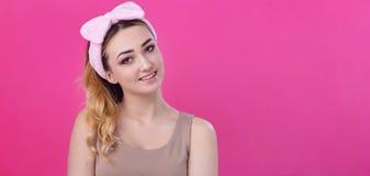 St?enden av en h?rlig flickakvinna i en huvudbindel f?r utg?r p? rosa studiobakgrund, begreppet av sk?nhet som annonserar sk?nhet arkivfoto