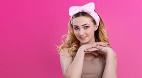 St?enden av en h?rlig flickakvinna i en huvudbindel f?r utg?r p? rosa studiobakgrund, begreppet av sk?nhet som annonserar sk?nhet royaltyfri foto