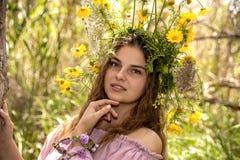St?enden av en ung kvinna i en krans av blommor st?nger sig upp med ett dr?mlikt uttryck p? hennes framsida arkivbild