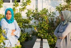 St?enden av ilskna tv? hijabkvinnor har mots?ttningar med grannar fotografering för bildbyråer
