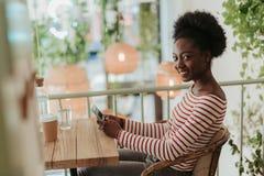 St?enden av lyckliga afrikanska kvinnan som den har, vilar i kaf? arkivbilder
