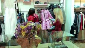 St?enden av tre h?rliga unga kvinnor som shoppar i kl?der, shoppar stock video