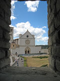 St. Francis of Assisi Church, located in Assisi, Italy. St. Francis of Assisi Church, with the town of Assisi in the background, framed by a window in a brick Royalty Free Stock Photography