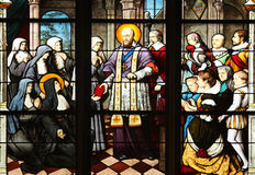 St. Francis de Sales handing Saint Jeanne de Chantal. In the constitutions of the Order of the Visitation, stained glass, Saint Severin church, Paris, France Royalty Free Stock Photography