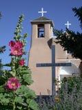 St. Francisco de la iglesia católica de Asisi con los Hollyhocks Foto de archivo