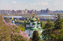 St. George Cathedral of the Vydubychi Monastery among the trees of the park against a modern apartment buildings spring Stock Photography