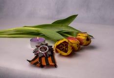 St. George Ribbon, Bestellung, brennende Kerze und ein Blumenstrauß von den Tulpen Stockfotos