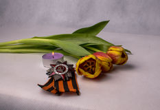 St. George Ribbon, Order, burning candle and a bouquet of tulips Stock Photos
