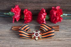 The St. George's ribbon and red carnations Stock Photography
