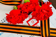 St- Georgeband und rote Gartennelken über dem Kalender mit am 9. Mai Datum Stockbild