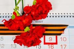 St- Georgeband und rote Gartennelken über dem Kalender mit am 9. Mai Datum Lizenzfreie Stockbilder