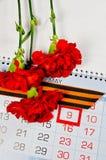 St- Georgeband und rote Gartennelken über dem Kalender mit am 9. Mai Datum Lizenzfreies Stockfoto