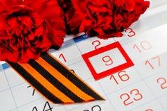 St- Georgeband und rote Gartennelken über dem Kalender mit am 9. Mai Datum Stockfoto