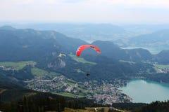 St Gilgen, Áustria: Paragliders vermelhos e amarelos que voam sobre as montanhas foto de stock royalty free